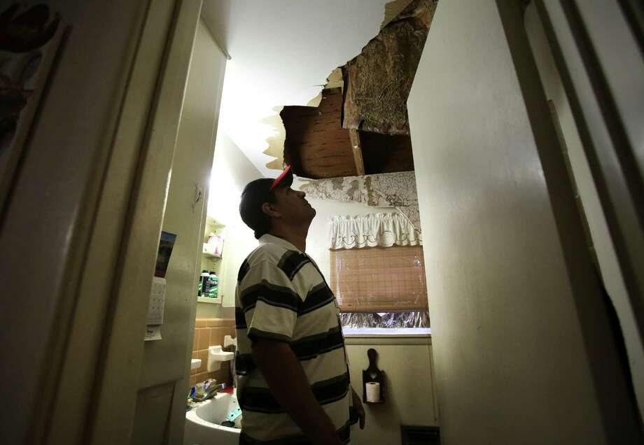 Pete Arias inspects the ceiling in the bathroom of his home in West, TX. Families were let back in to see their homes which were damaged by the explosion in West, TX on Sunday April 21, 2013. Photo: Bob Owen, Express-News / ©2013 San Antonio Express-News