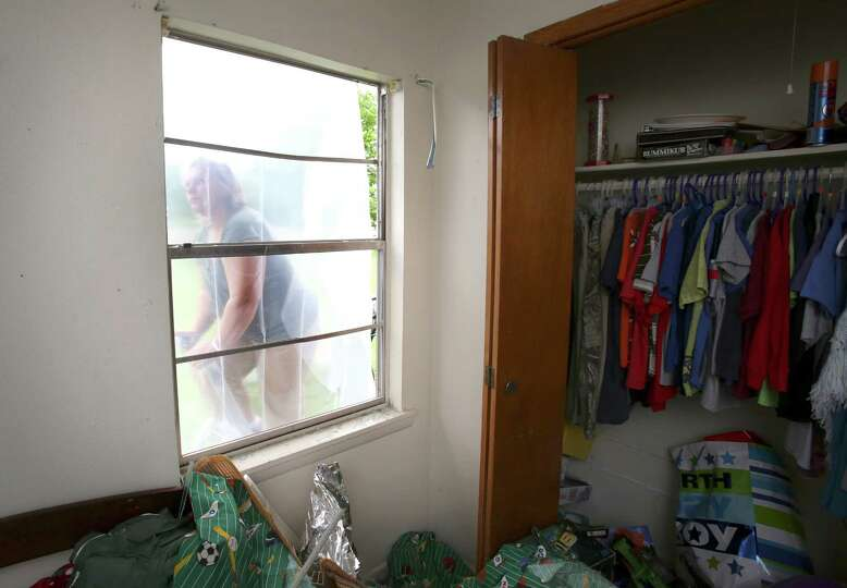 Jacki Arias, left, climbs a ladder to cover a broken window with plastic at her home in West, TX. th