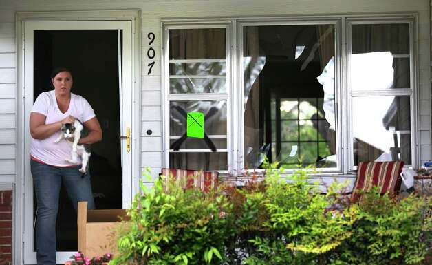 A West resident steps out of a shattered glass storm door carrying her cat, after being allowed return to her home for the first time since the explosion, on Sunday April 21, 2013. Photo: Bob Owen, Express-News / ©2013 San Antonio Express-News
