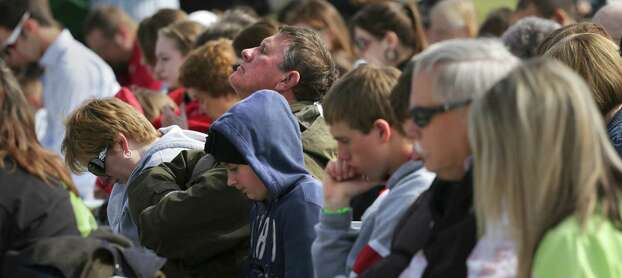 An unidentified man lifts his face to heaven with other members of First Baptist Church in prayer during an outside service due to damaged to the church's building from the explosion in West, on Sunday April 21, 2013. Photo: Bob Owen, Express-News / ©2013 San Antonio Express-News