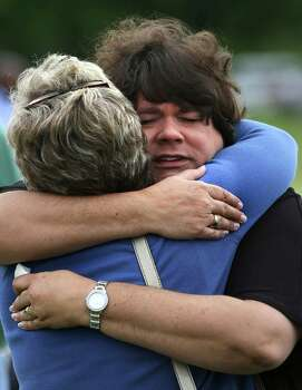 Lisa Crowder, right, recieves a hug from Shelly Miller as the two attend an outdoor service held by First Baptist Church in West, whose building is too damaged to hold worship on Sunday April 21, 2013. Crowder and her husband, Pastor John Crowder lost their home to the explosion. Photo: Bob Owen, Express-News / ©2013 San Antonio Express-News