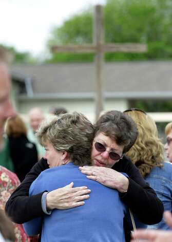 Shelly Miller, in light blue, gives and receives a hug from a fellow member of First Baptist Church at a service that was held outside due to damage done their church building in West, on Sunday April 21, 2013. Photo: Bob Owen, Express-News / ©2013 San Antonio Express-News