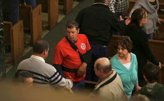 An unidentified injured member of the West VFD is greeted by a church member as they pass the peace at Church of the Assumption in West, TX on Sunday April 21, 2013. Photo: Bob Owen, Express-News / ©2013 San Antonio Express-News