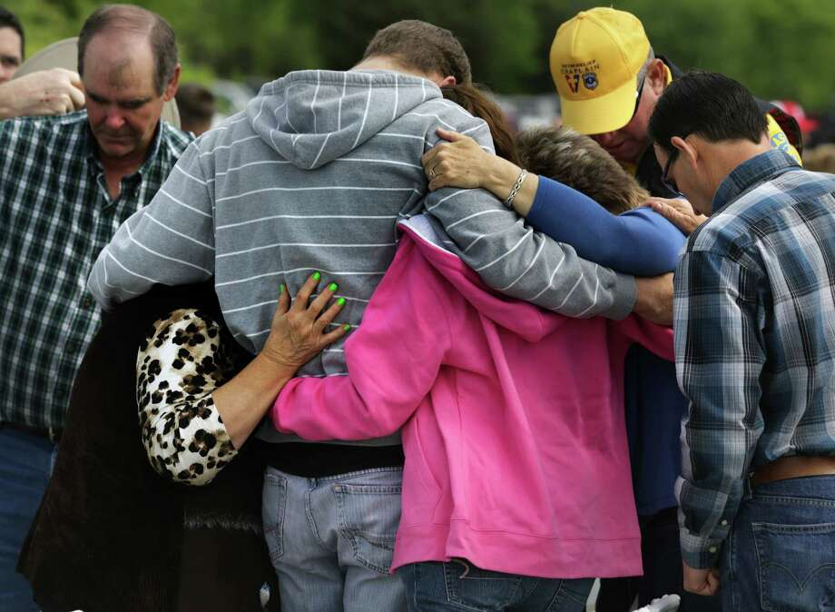 Members of West's damaged First Baptist Church comfort Patrick Weaver (gray hoodie) and friend Rachal (pink) after a service in a hayfield. Photo: Bob Owen, Express-News / ©2013 San Antonio Express-News