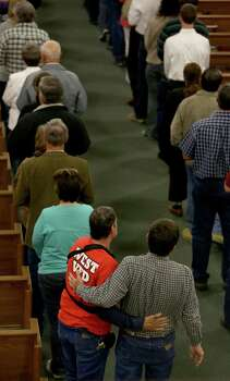 An unidentified injured member of the West VFD is greeted by a church member as they stand in line to receive communion at Church of the Assumption in West, TX on Sunday April 21, 2013. Photo: Bob Owen, Express-News / ©2013 San Antonio Express-News