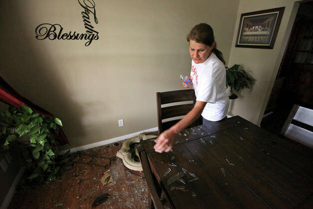 Trish Webre removes shattered window glass from her table, Sunday April 21, 2013, in her home that was damaged by an explosion at a fertilizer plant that occurred Wednesday evening in West, Tx. Photo: Edward A. Ornelas, Express-News / © 2013 San Antonio Express-News