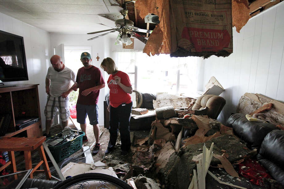 Scott Tacker (second from left) and his wife Jennifer Tacker get help from Jennifer's brother Will Matus (left) as they retrieve belongings, Sunday April 21, 2013, from their home that was damaged by an explosion at a fertilizer plant that occurred Wednesday evening in West, Tx. Photo: Edward A. Ornelas, Express-News / © 2013 San Antonio Express-News