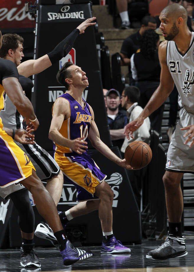 Lakers guard Steve Nash tries to shoot under the basket between the Spurs' Tiago Splitter (left) and Tim Duncan. Nash had 16 points in 29 minutes in his first action since March 30. Photo: Jerry Lara / San Antonio Express-News