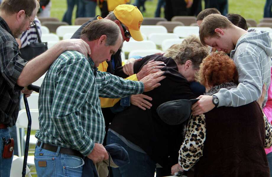 Patrick Weaver, far right, is prayed over by members of West's First Baptist Church on Sunday. The service was held outside because of damage to their church building from the Wednesday fertilizer plant explosion that killed 14 people. Photo: Mayra Beltran, Staff / © 2013 Houston Chronicle