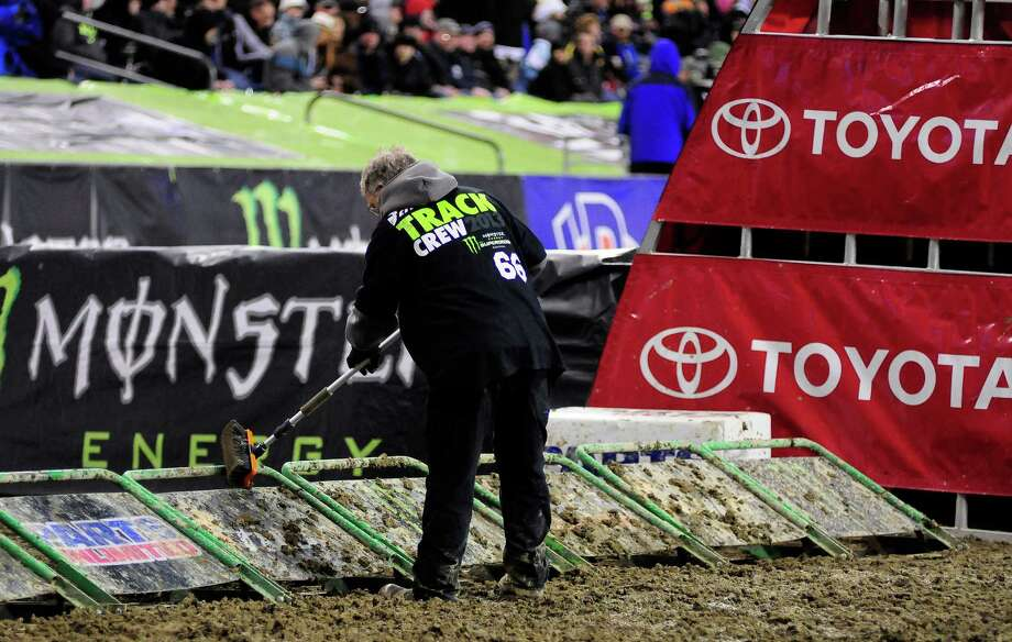 A member of the track crew helps clean off particularly muddy starter gates at the Monster Energy AMA Supercross at CenturyLink Field on Saturday, April 20, 2013. Several wipeouts occurred throughout the night due to a muddy track from the afternoon's heavy rain. Justin Barcia of Pinetta, Fla. took the main event of the night, placing Seattle-favorite Ryan Villopoto in second. Photo: LINDSEY WASSON, Seattlepi.com / SEATTLEPI.COM