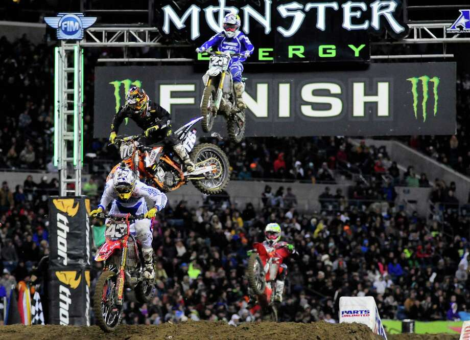 Riders catch some air as they finish a lap during the 450SX Main Event at the Monster Energy AMA Supercross at CenturyLink Field on Saturday, April 20, 2013. Several wipeouts occurred throughout the night due to a muddy track from the afternoon's heavy rain. Justin Barcia of Pinetta, Fla. took the main event of the night, placing Seattle-favorite Ryan Villopoto in second. Photo: LINDSEY WASSON, Seattlepi.com / SEATTLEPI.COM