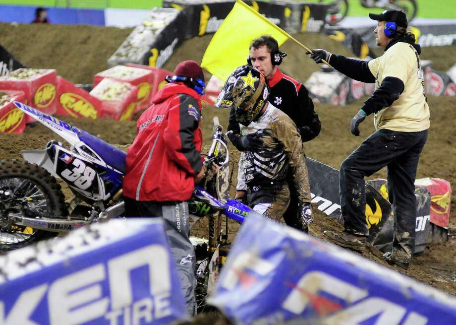 Kyle Cunningham looks dejected as he is helped up after a muddy fall at the Monster Energy AMA Supercross at CenturyLink Field on Saturday, April 20, 2013. Several wipeouts occurred throughout the night due to a muddy track from the afternoon's heavy rain. Justin Barcia of Pinetta, Fla. took the main event of the night, placing Seattle-favorite Ryan Villopoto in second. Photo: LINDSEY WASSON, Seattlepi.com / SEATTLEPI.COM