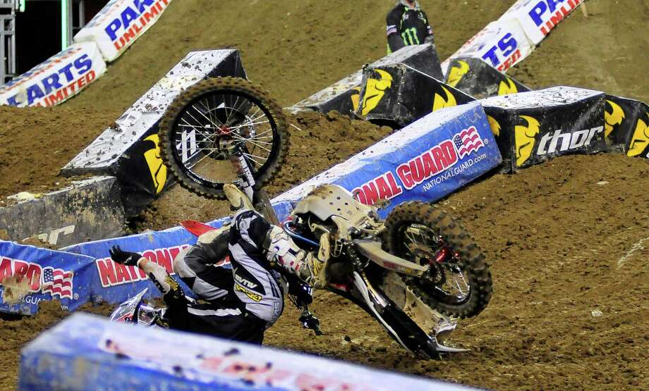 Eli Tomac tries unsuccessfully to keep his bike from falling on him as he wipes out during the 450SX Main Event at the Monster Energy AMA Supercross at CenturyLink Field on Saturday, April 20, 2013. Several wipeouts occurred throughout the night due to a muddy track from the afternoon's heavy rain. Justin Barcia of Pinetta, Fla. took the main event of the night, placing Seattle-favorite Ryan Villopoto in second. Photo: LINDSEY WASSON, Seattlepi.com / SEATTLEPI.COM