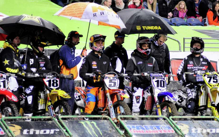 Several racers are covered by umbrellas despite their helmets and impending muddiness before a race at the Monster Energy AMA Supercross at CenturyLink Field on Saturday, April 20, 2013. Several wipeouts occurred throughout the night due to a muddy track from the afternoon's heavy rain. Justin Barcia of Pinetta, Fla. took the main event of the night, placing Seattle-favorite Ryan Villopoto in second. Photo: LINDSEY WASSON, Seattlepi.com / SEATTLEPI.COM