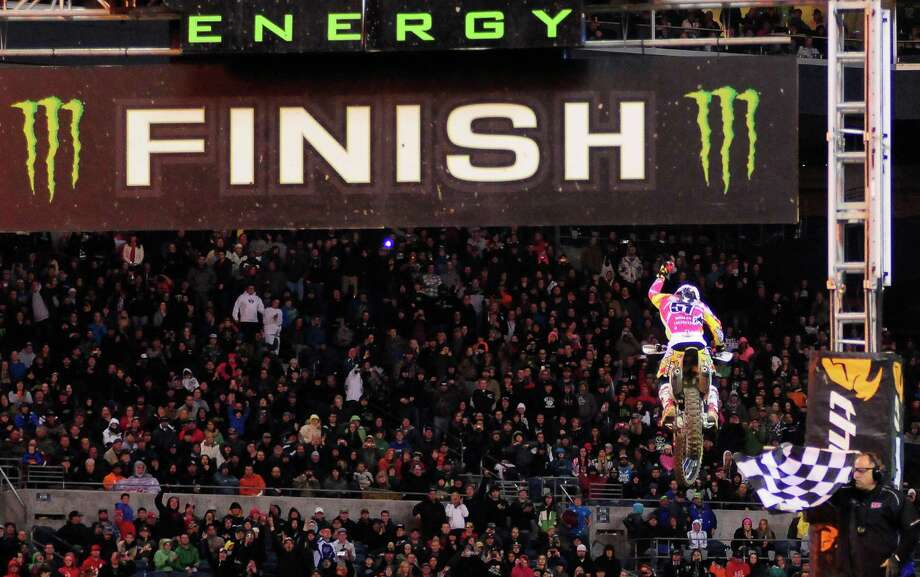 Justin Barcia, illuminated by a ball of fire, raises his hand in the air as he wins the 450SX Main Event at the Monster Energy AMA Supercross at CenturyLink Field on Saturday, April 20, 2013. Several wipeouts occurred throughout the night due to a muddy track from the afternoon's heavy rain. Justin Barcia of Pinetta, Fla. took the main event of the night, placing Seattle-favorite Ryan Villopoto in second. Photo: LINDSEY WASSON, Seattlepi.com / SEATTLEPI.COM