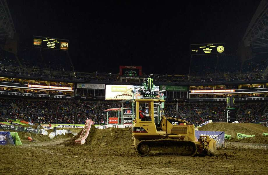 One of a group of bulldozers works to smooth an overly muddy track at the Monster Energy AMA Supercross at CenturyLink Field on Saturday, April 20, 2013. Several wipeouts occurred throughout the night due to a muddy track from the afternoon's heavy rain. Justin Barcia of Pinetta, Fla. took the main event of the night, placing Seattle-favorite Ryan Villopoto in second. Photo: LINDSEY WASSON, Seattlepi.com / SEATTLEPI.COM