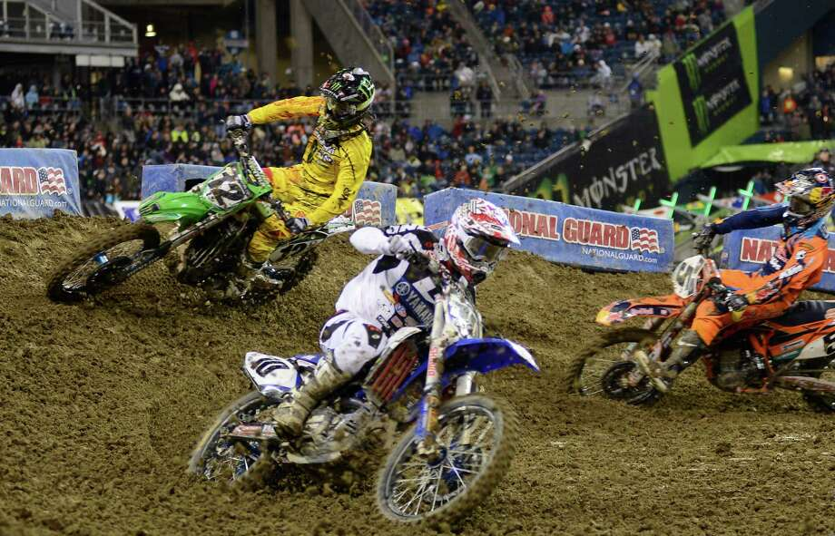 Racers come out of a turn during the 450SX Main Event at the Monster Energy AMA Supercross at CenturyLink Field on Saturday, April 20, 2013. Several wipeouts occurred throughout the night due to a muddy track from the afternoon's heavy rain. Justin Barcia of Pinetta, Fla. took the main event of the night, placing Seattle-favorite Ryan Villopoto in second. Photo: LINDSEY WASSON, Seattlepi.com / SEATTLEPI.COM