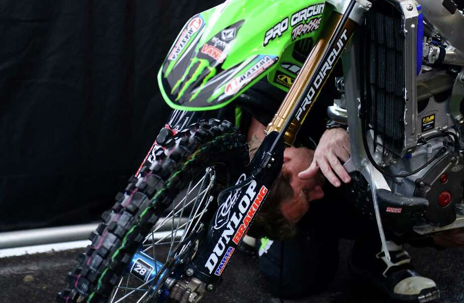 Wayne Lumgair tends to a Monster Kawasaki bike before the races at the Monster Energy AMA Supercross at CenturyLink Field on Saturday, April 20, 2013. Several wipeouts occurred throughout the night due to a muddy track from the afternoon's heavy rain. Justin Barcia of Pinetta, Fla. took the main event of the night, placing Seattle-favorite Ryan Villopoto in second. Photo: LINDSEY WASSON, Seattlepi.com / SEATTLEPI.COM