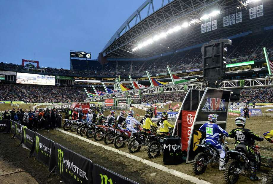 Riders idle at the start gate before the second qualifying heat for the 250SX class at the Monster Energy AMA Supercross at CenturyLink Field on Saturday, April 20, 2013. Several wipeouts occurred throughout the night due to a muddy track from the afternoon's heavy rain. Justin Barcia of Pinetta, Fla. took the main event of the night, placing Seattle-favorite Ryan Villopoto in second. Photo: LINDSEY WASSON, Seattlepi.com / SEATTLEPI.COM