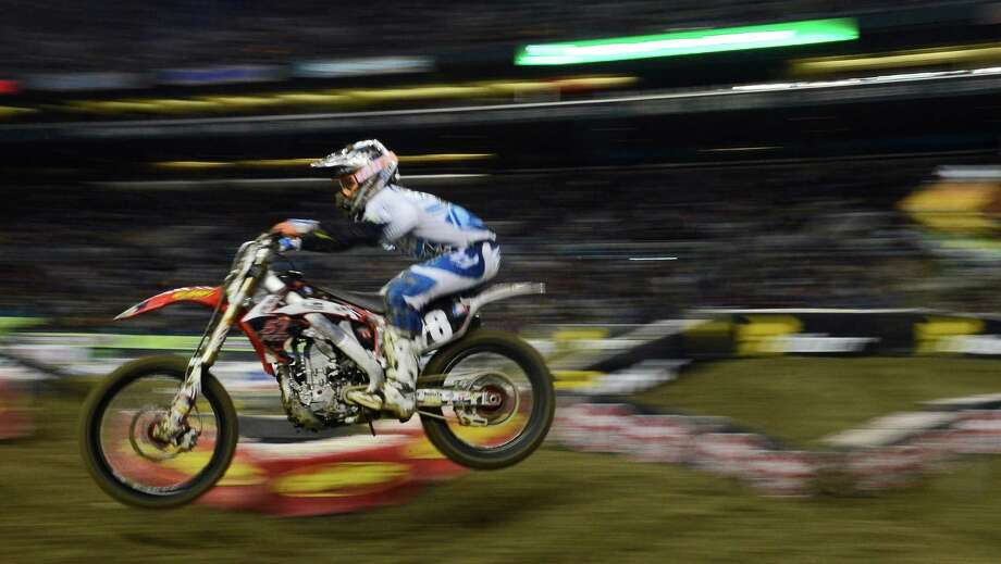 Scott Champion is a blur during the 2nd qualifying heat of the 250SX class at the Monster Energy AMA Supercross at CenturyLink Field on Saturday, April 20, 2013. Several wipeouts occurred throughout the night due to a muddy track from the afternoon's heavy rain. Justin Barcia of Pinetta, Fla. took the main event of the night, placing Seattle-favorite Ryan Villopoto in second. Photo: LINDSEY WASSON, Seattlepi.com / SEATTLEPI.COM