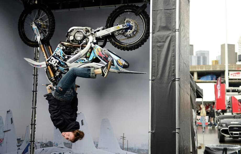 Jill Green has her photo taken as she hangs from a bike suspended several feet in the air outside the Monster Energy AMA Supercross at CenturyLink Field on Saturday, April 20, 2013. Several wipeouts occurred throughout the night due to a muddy track from the afternoon's heavy rain. Justin Barcia of Pinetta, Fla. took the main event of the night, placing Seattle-favorite Ryan Villopoto in second. Photo: LINDSEY WASSON, Seattlepi.com / SEATTLEPI.COM