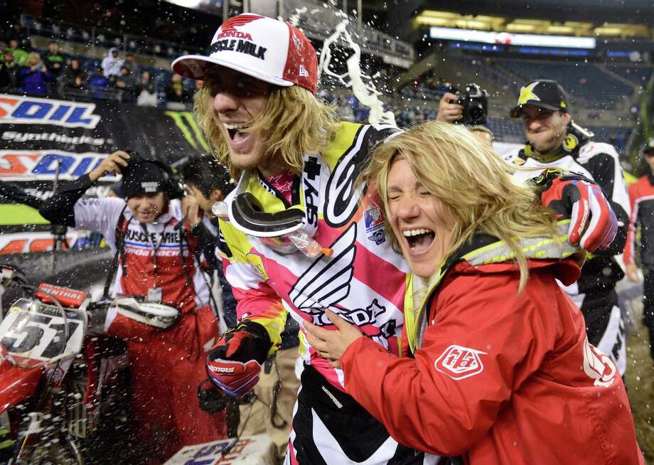 450SX class winner Justin Barcia, center, and a member of his crew laugh as they are caught in a champagne celebration sneak-attack from third-place winner David Millsaps, far right, at the Monster Energy AMA Supercross at CenturyLink Field on Saturday, April 20, 2013. Poulsbo resident and Seattle favorite Ryan Villopoto finished second in the event. Photo: LINDSEY WASSON, Seattlepi.com / SEATTLEPI.COM