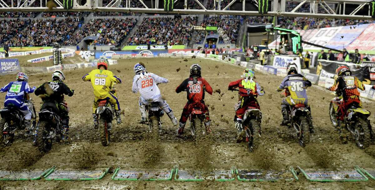 Riders kick up a spray of dirt shooting back at least 20 feet as they begin the 250SX class second qualifying heat at the Monster Energy AMA Supercross at CenturyLink Field on Saturday, April 20, 2013. Several wipeouts occurred throughout the night due to a muddy track from the afternoon's heavy rain. Justin Barcia of Pinetta, Fla. took the main event of the night, placing Seattle-favorite Ryan Villopoto in second.