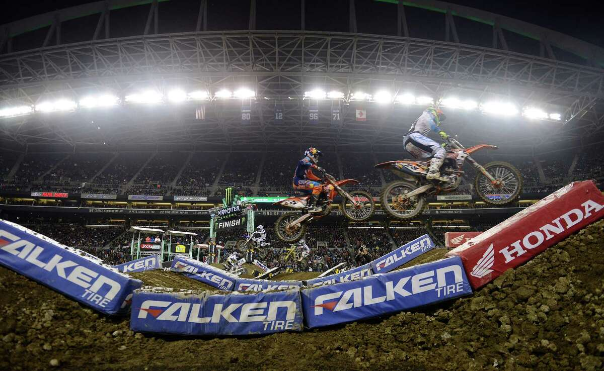 Ryan Dungey, center, and Jake Canada, right, catch some air off a jump during the 450SX Main Event at the Monster Energy AMA Supercross at CenturyLink Field on Saturday, April 20, 2013. Several wipeouts occurred throughout the night due to a muddy track from the afternoon's heavy rain. Justin Barcia of Pinetta, Fla. took the main event of the night, placing Seattle-favorite Ryan Villopoto in second.
