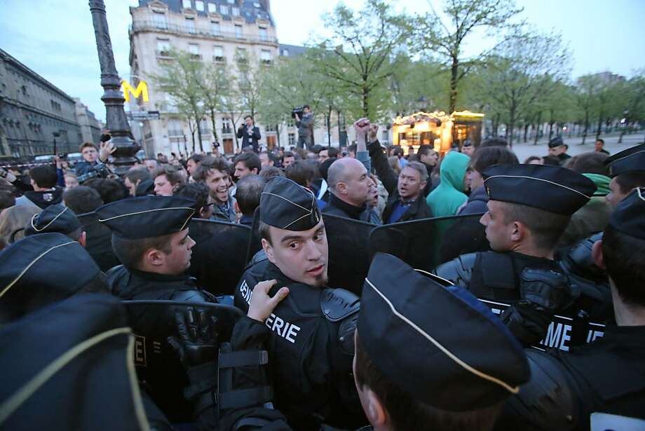 Demonstrators scuffle with riot police on the sideline of a rally to protest against French President Francois Hollande's social reform on gay marriage and adoption in Paris, Sunday, April 21, 2013. Both houses of the French parliament have already approved the bill in a first reading. The second and final reading is expected Tuesday. (AP Photo/Michel Euler) Photo: Michel Euler, Associated Press