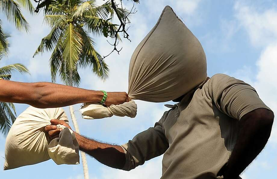New Year's Eve bash:Sri Lankan men pummel each other with bags of linens in an attempt to knock each other off a balance beam in Colombo. The game is a tradition during Sinhala and Tamil New Year celebrations on the island. Photo: Larkruwan Wanniarachchi, AFP/Getty Images