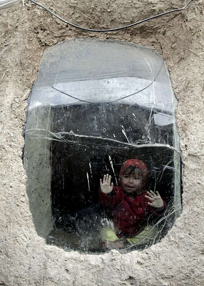 The girl in the terrarium: An Afghan child explores the limits of a convex window at her temporary home on the outskirts of Kabul. Photo: Rahmat Gul, Associated Press