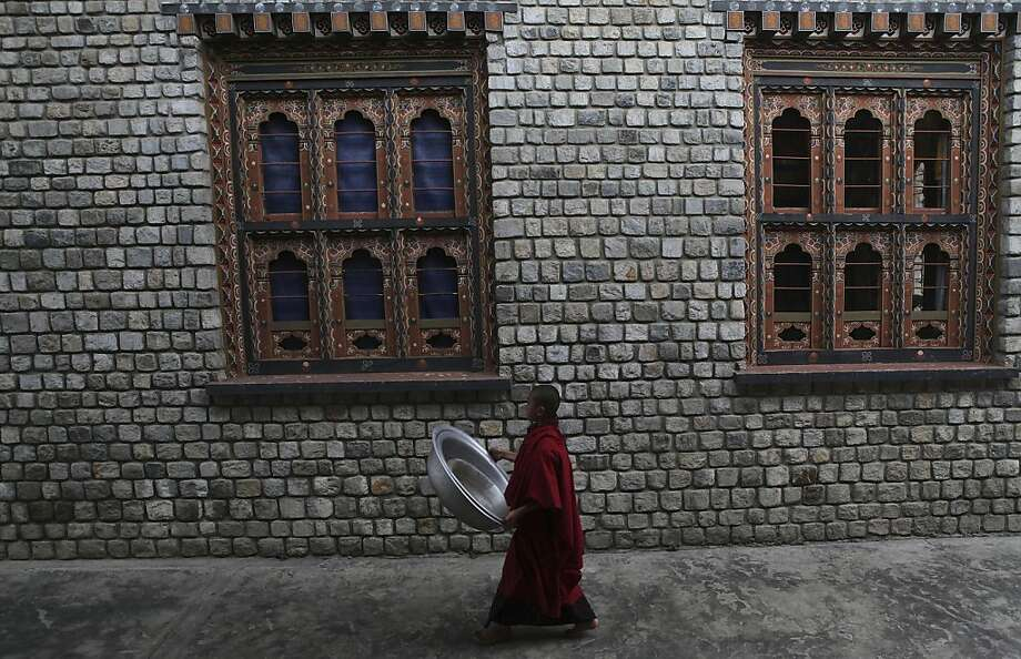 A Monk walks outside a Buddhist monastery in Dratshang, Bhutan, Sunday, April 21, 2013. Known by its people as the Land of the Thunder Dragon, Bhutan's snowcapped peaks and mountainside monasteries have long intrigued Westerners in search of a Buddhist nirvana. (AP Photo/Anupam Nath) Photo: Anupam Nath, Associated Press