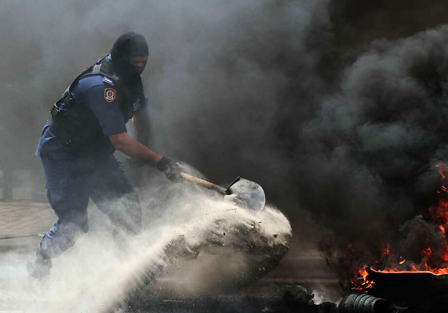 A riot policeman extinguishes a row of burning tires set ablaze by Bahraini anti-government protesters, not pictured, on a street in Jidhafs, Bahrain, Sunday, April 21, 2013. (AP Photo/Hasan Jamali) Photo: Hasan Jamali, Associated Press