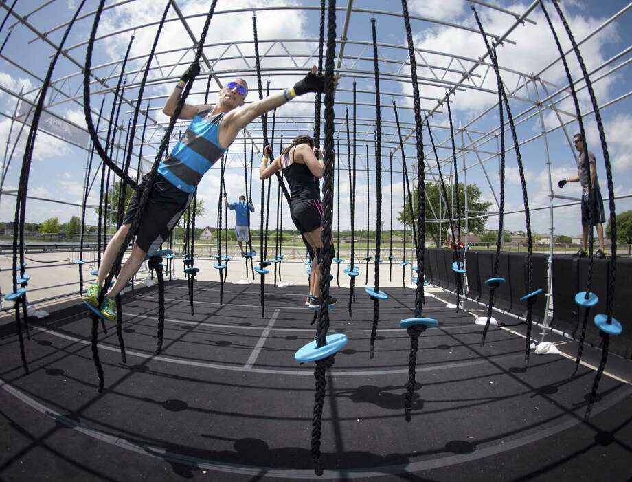 "Competitors test their fitness in the ""sea of ropes"" portion of the Alpha Warrior event Sunday at Retama Park. Photo: Darren Abate / For The San Antonio Express-News"