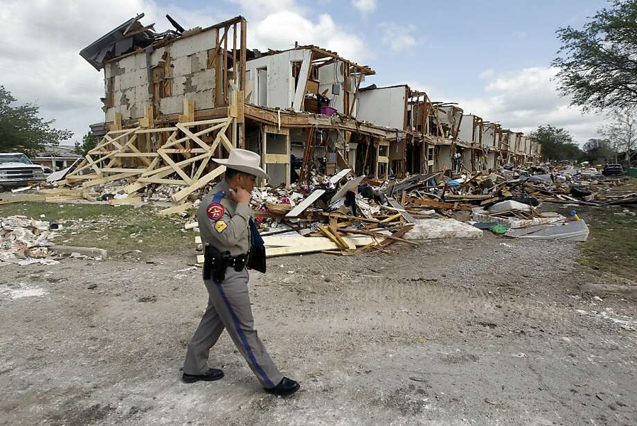 DPS Sgt. Jason Reyes walks past an apartment complex, pictured on April 21, 2013, near the West Fertilizer plant explosion was destroyed from the blast in West, Texas. (Pool photo by Michael Ainsworth/Dallas Morning News/MCT) Photo: Michael Ainsworth, McClatchy-Tribune News Service
