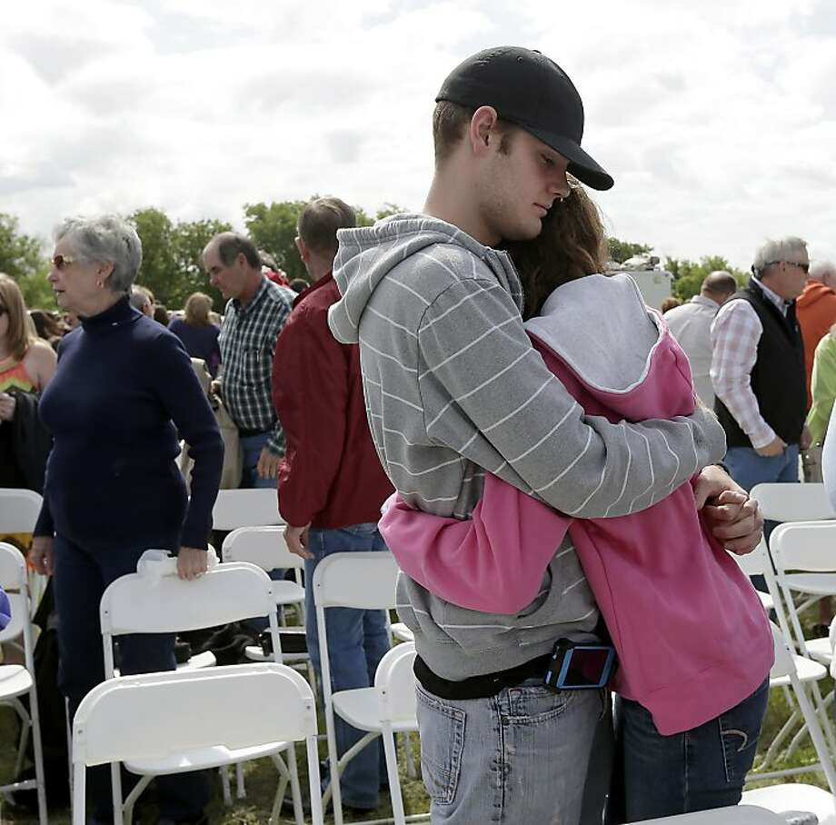 Patrick Weaver hugs a friend after an outdoor service for the First Baptist Church in a field Sunday, April 21, 2013, four days after an explosion at a fertilizer plant in West, Texas. Weaver's home was destroyed after a massive explosion at the West Fertilizer Co. Wednesday night that killed 14 people and injured more than 160. (AP Photo/Charlie Riedel) Photo: Charlie Riedel, Associated Press