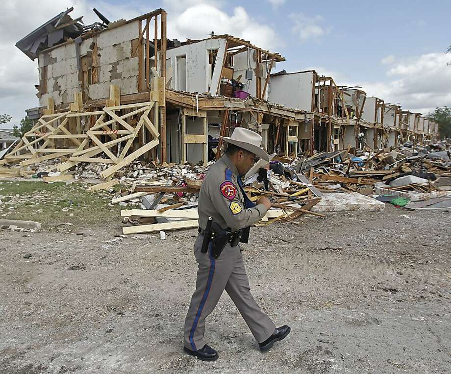 Texas Department of Public Safety Sgt. Jason Reyes walks past a damaged apartment complex, Sunday, April 21, 2013, four days after an explosion at a fertilizer plant in West, Texas. The massive explosion at the West Fertilizer Co. Wednesday night killed 14 people and injured more than 160. (AP Photo/The Dallas Morning News, Michael Ainsworth, Pool) Photo: Michael Ainsworth, Associated Press