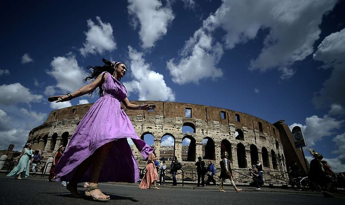 Fares from SFO to Rome plummet to record lows for spring trips. Picture: Women belonging to historical groups march dressed as ancient Romans during a parade in front of the coliseum to mark the anniversary of the legendary foundation of the eternal city in 753 B.C, in Rome on April 21, 2013. AFP PHOTO / Filippo MONTEFORTEFILIPPO MONTEFORTE/AFP/Getty Images