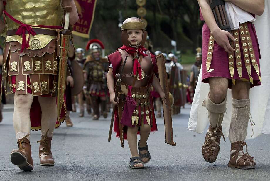 "Merry she-wolf foster parent day! A lightweight Legionnaire marches during ""Christmas of Rome,"" the celebration of the founding of the Eternal City by Romulus in 753 B.C. Photo: Andrew Medichini, Associated Press"