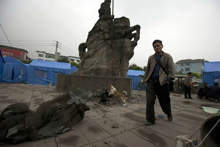 A man walks past a statue of a horseman damaged by Saturday's earthquake in Lushan county, in southwestern China's Sichuan province, Monday, April 22, 2013. Saturday's earthquake in Sichuan province killed at least 186 people, injured more than 11,000 and left nearly two dozen missing, mostly in the rural communities around Ya'an city, along the same seismic fault where a devastating quake to the north killed more than 90,000 people in Sichuan and neighboring areas five years ago in one of China's worst natural disasters.(AP Photo/Ng Han Guan) Photo: Ng Han Guan, Associated Press