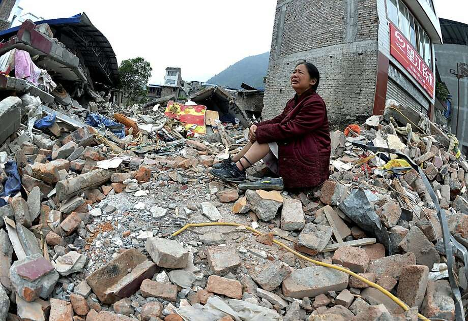 A woman whose relatives were killed in Saturday's earthquake cries while sitting on a pile of rubble in Lingguan township in Baoxing county of southwest China's Sichuan province on Sunday, April 21, 2013. Saturday's earthquake in Sichuan province killed at least 186 people, injured more than 11,000 and left nearly two dozen missing, mostly in the rural communities around Ya'an city, along the same fault line where a devastating quake to the north killed more than 90,000 people in Sichuan and neighboring areas five years ago in one of China's worst natural disasters. (AP Photo) CHINA OUT Photo: Associated Press