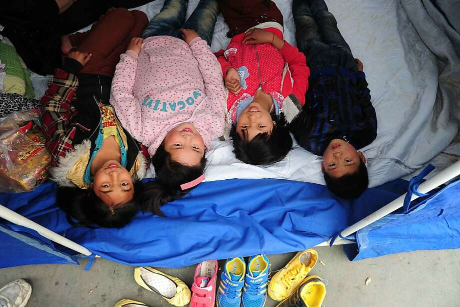 Chinese kids lie on their bed in the temporary settlement in Longmen township, a town close to the epicentre of the earthquake that hit the city in Ya'an, southwest China's Sichuan province on April 21, 2013. Thousands of rescue workers combed through flattened villages in southwest China on Sunday in a race to find survivors from a powerful quake as the toll of dead and missing rose past 200. CHINA OUT   AFP PHOTOSTR/AFP/Getty Images Photo: Str, AFP/Getty Images