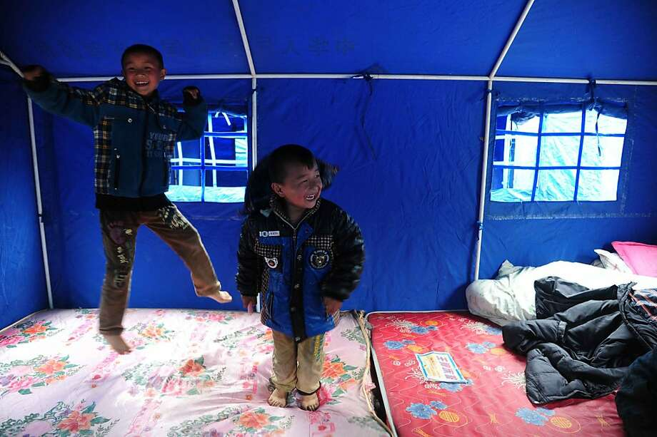 Chinese kids play in their tents in the temporary settlement in Longmen township, a town close to the epicentre of the earthquake that hit the city in Ya'an, southwest China's Sichuan province on April 21, 2013. Thousands of rescue workers combed through flattened villages in southwest China on Sunday in a race to find survivors from a powerful quake as the toll of dead and missing rose past 200. CHINA OUT   AFP PHOTOSTR/AFP/Getty Images Photo: Str, AFP/Getty Images