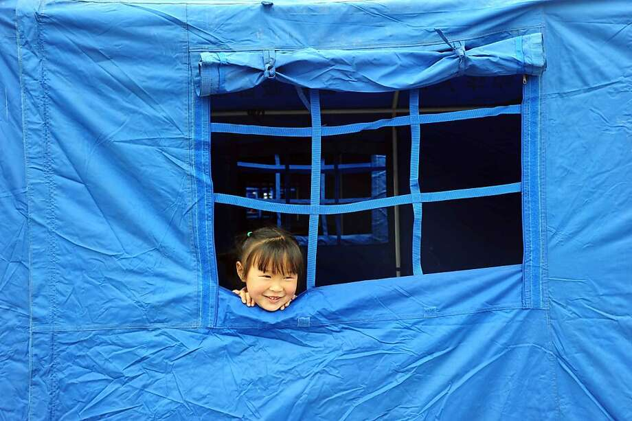 A little girl looks on from the window of a tent in the temporary settlement in Longmen township, a town close to the epicentre of the earthquake that hit the city in Ya'an, southwest China's Sichuan province on April 21, 2013. Thousands of rescue workers combed through flattened villages in southwest China on Sunday in a race to find survivors from a powerful quake as the toll of dead and missing rose past 200. CHINA OUT   AFP PHOTOSTR/AFP/Getty Images Photo: Str, AFP/Getty Images
