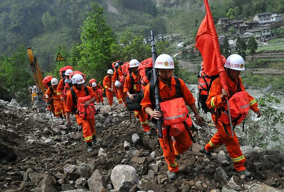 Chinese rescuers walk through wreckage to reach isolated Baoxing country after the earthquake in Ya'an, southwest China's Sichuan province on April 21, 2013. Thousands of rescue workers combed through flattened villages in southwest China on Sunday in a race to find survivors from a powerful quake as the toll of dead and missing rose past 200. CHINA OUT   AFP PHOTOSTR/AFP/Getty Images Photo: Str, AFP/Getty Images