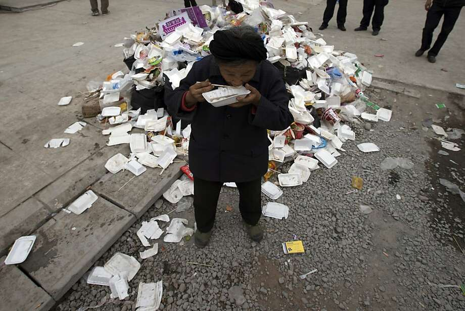 An elderly woman eats a meal near rubbish piled up at a center for evacuees in the county seat of Lushan in southwestern China's Sichuan province, Sunday, April 21, 2013. Rescuers and relief teams struggled to rush supplies into the rural hills of China's Sichuan province Sunday after the earthquake prompted frightened survivors to spend a night in cars, tents and makeshift shelters. (AP Photo/Ng Han Guan) Photo: Ng Han Guan, Associated Press