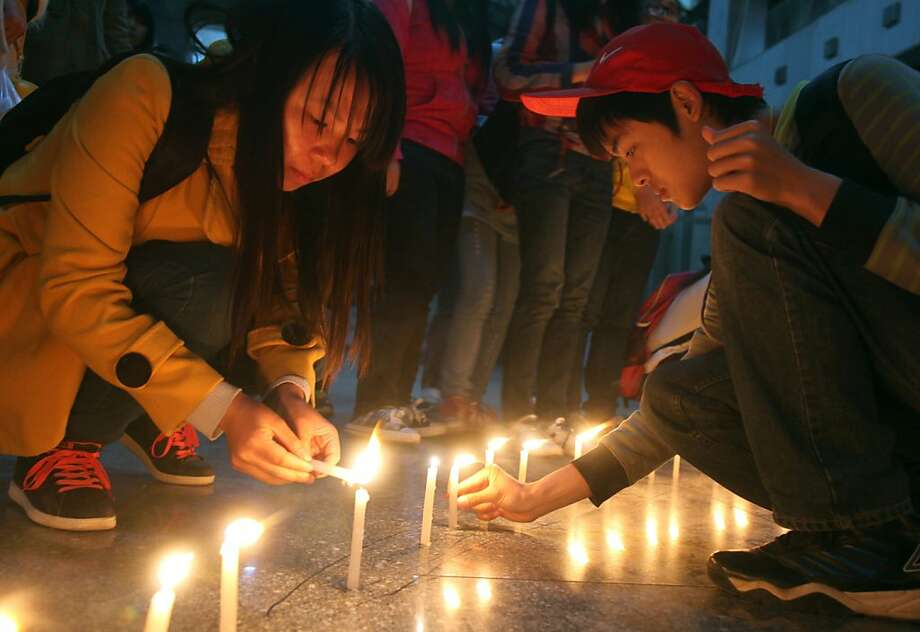 This picture taken on April 20, 2013 shows college students praying for people at their campus in Hengyang, central China's Hunan province, after an earthquake of 7.0 hit the city of Ya'an, southwest China's Sichuan province in the early morning of April 20.  Thousands of rescue workers combed through flattened villages in southwest China in a race to find survivors from a powerful quake as the toll of dead and missing rose past 200.   CHINA OUT   AFP PHOTOSTR/AFP/Getty Images Photo: Str, AFP/Getty Images