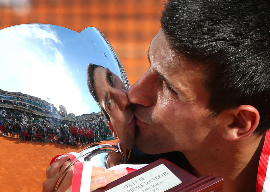 Novak Djokovic kisses the Monte Carlo Masters trophy after ending Rafael Nadal's eight-year reign with a 6-2, 7-6 (1) win. Photo: Claude Paris / Associated Press