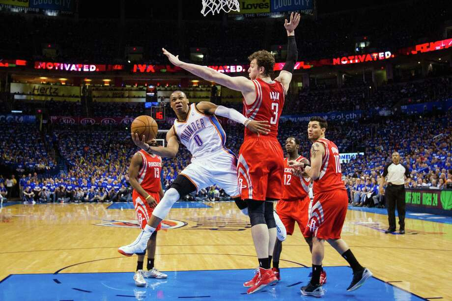 Oklahoma City Thunder point guard Russell Westbrook (0) drives to the basket past Houston Rockets center Omer Asik (3) during the first half of Game 1 of a Western Conference first-round playoff series at Chesapeake Arena on Sunday, April 21, 2013, in Oklahoma City. Photo: Smiley N. Pool, Houston Chronicle / © 2013  Houston Chronicle