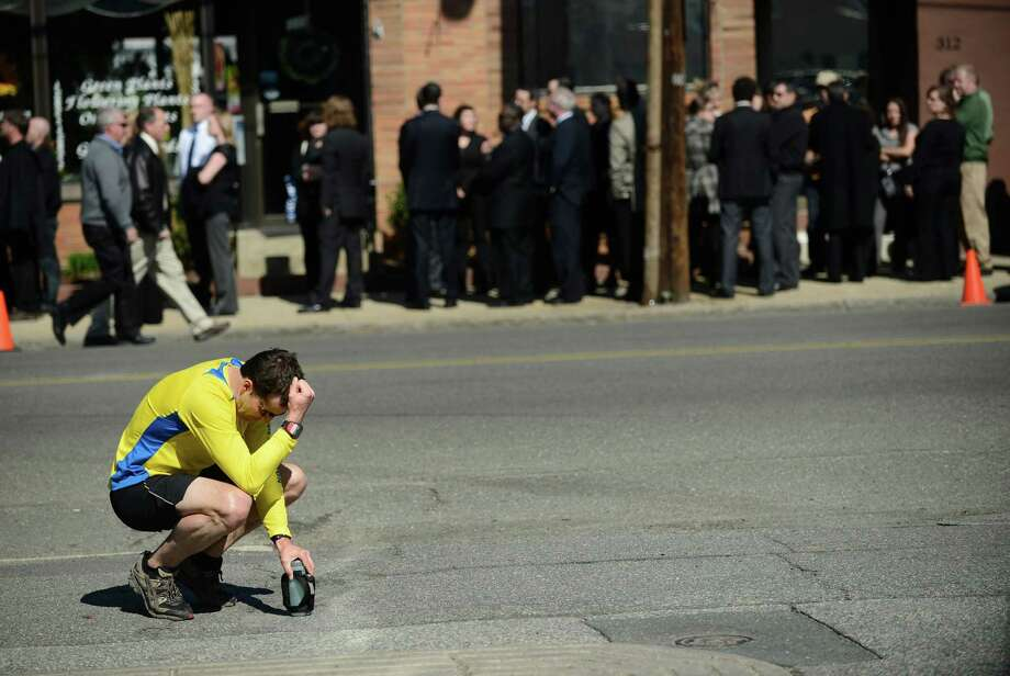 A runner pauses to reflect as friends and family of Krystle Campbell, one of the three people killed in the Boston bombing, gather for her wake in Medford, Mass., April 21, 2013. With the surviving suspect of the bombing in the hospital ? a breathing tube down his throat and unable to speak ? several lawmakers said Sunday that he should be tried in federal court as a civilian, a move that would allow prosecutors to seek the death penalty. (Gretchen Ertl/The New York Times) Photo: GRETCHEN ERTL / NYTNS